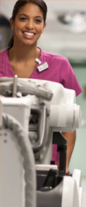 A smiling woman in pink scrubs pushes a portable x-ray machine.