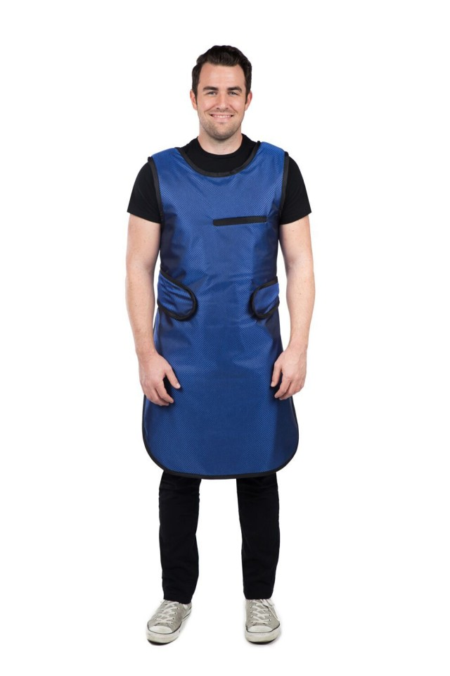 A male radiology technician wears a blue, full-length lead apron, an important radiation protection device for lab staff members.