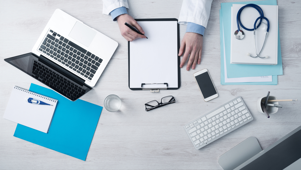 Pictured are the hands of someone in a lab coat writing on a clipboard with computer, glasses, a phone and computers on the desk. The doctor is perhaps calculating his Section 179 deduction for medical equipment.