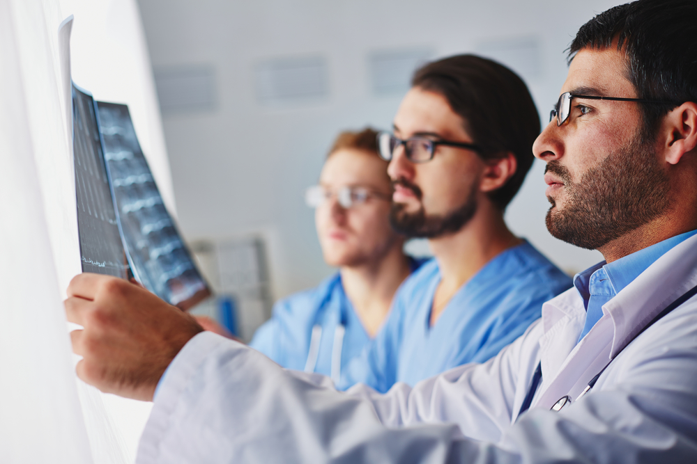 3 young male doctors are looking at a patient's X-ray, with the doctor in the foreground holding the scan against a light board. Improvements in computer technology are shaping the future of radiology.